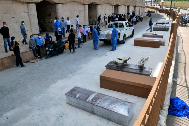 People wait next to coffins and cardboard boxes to bury their loved ones outside a cemetery in Guayaquyil, Ecuador, April 6, 2020.