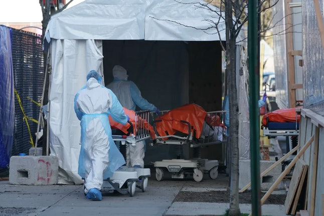 Bodies are moved to a refrigerated truck serving as a temporary morgue for Wyckoff Hospital, Brooklyn, April 4, 2020 in New York City, where someone dies from COVID-19 every few minutes.
