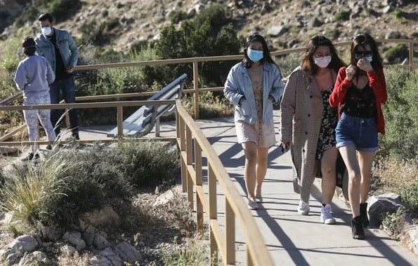 Visitors wear face masks at Joshua Tree National Park in California on May 18, 2020. Wearing masks and keeping at least six feet apart are still important.