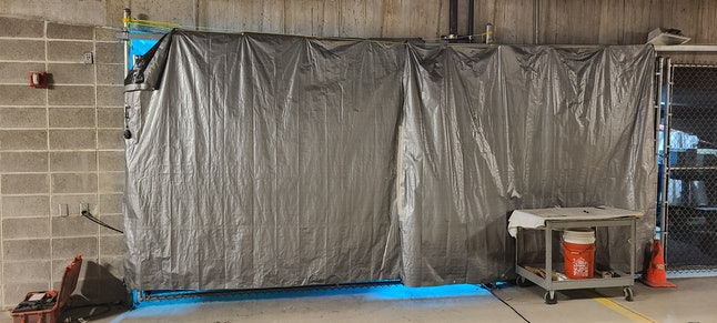 At the Dane County Jail in Madison, Wisconsin, a robot that emits ultraviolet light is behind a tarp, which is used to protect people from exposure to the machine's powerful rays.