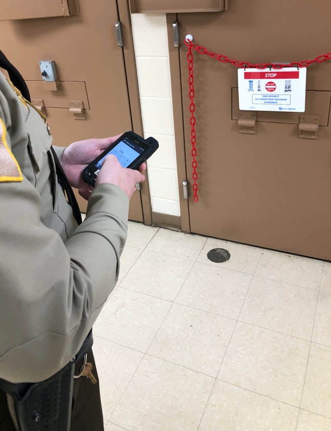 An officer at the Jefferson County Jail in Madison, Indiana, uses a handheld device to operate a machine that emits strong ultraviolet light, which is being used to disinfect the jail in the fight against coronavirus.