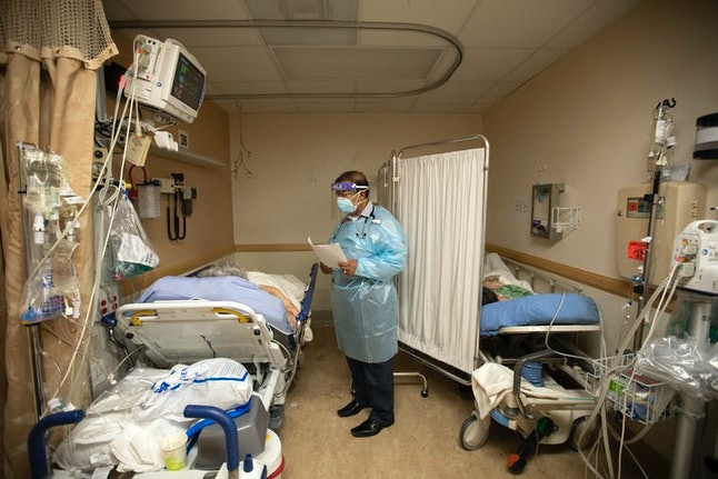A doctor checks on patients in a temporary space at an overloaded hospital near Los Angeles.