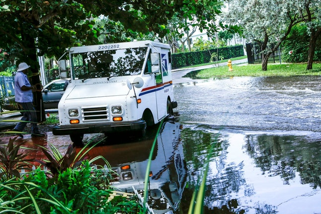 A postal worker returns to their truck parked on a flooded street a few miles from the downtown Miami venue where the first Democratic presidential debate will be held. Some consider Miami the Ground Zero for any climate-related sea level rise in the United States. Many local residents and coastal community leaders will be listening for any proposals to stave off the effects of rising seas