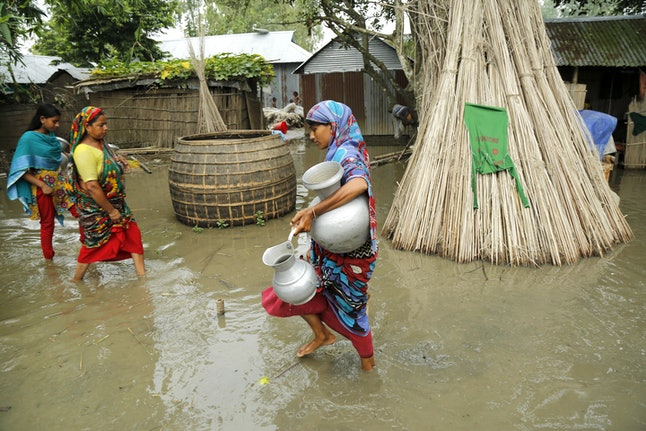 Flood victims return their temporary shelters in an embankment after collecting drinking water near a river island formed from sedimentation, known as a 'char' at Mainkdir, Sariakandi, Bogra, Bangladesh, 16 August 2017. Flood victims are facing severe shortages of drinking water and food. Many flood victims have abandoned their homes along with their cattle, goats, to take shelter on embankments. At least 50 people have died as a result of the floods.