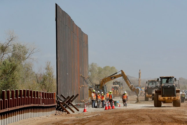 Government contractors erect a section of Pentagon-funded border wall along the Colorado River, in Yuma, Ariz. The 30-foot high wall replaces a five-mile section of Normandy barrier and post-n-beam fencing, shown at left, along the the International border that separates Mexico and the United States. Construction began as federal officials revealed a list of Defense Department projects to be cut to pay for President Donald Trump's wall