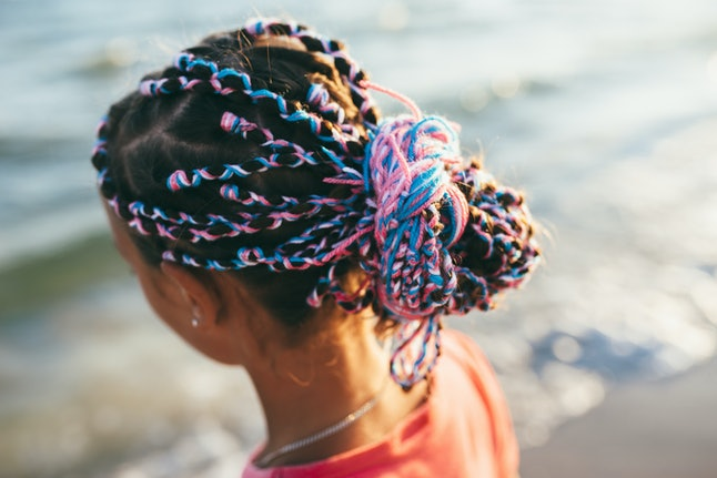Handsome girl kid with bright colored afro braids. creative hairstyle