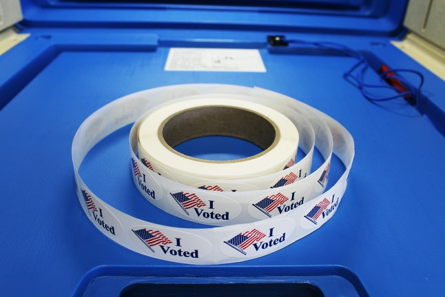 "Red white and blue ""I voted"" stickers with American flag are on a spool of stickers placed on a voting booth platform."