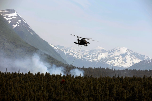 "Alaska Army National Guard Black Hawk crews help fight Alaska fires. From the Alaska Army National Guard, a ""Bambi Bucket,"" hanging from an ANG Black Hawk helicopter releases hundreds of gallons of water onto the Stetson Creek Fire near Cooper Landing, Alaska. Crews have wrangled two large wildfires north and south of Anchorage as dozens of blazes burn about 160 square miles in Alaska. One fire forced the evacuation of campsites on the Kenai Peninsula and destroyed at least eight structures since Monday. Altogether, 49 active fires are burning in three western states"