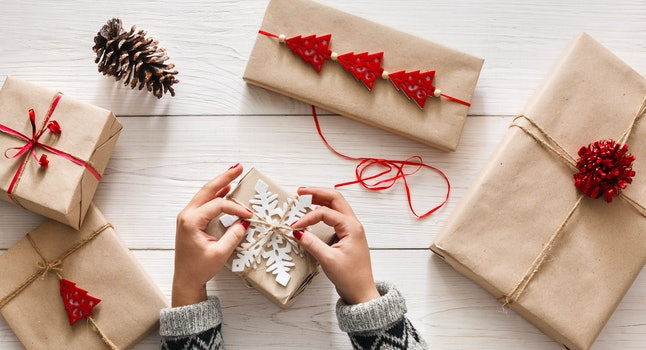 Creative hobby. Woman's hands wrap christmas holiday handmade present in craft paper with twine ribbon. Making bow at xmas gift box, decorated with snowflake on white wooden table, top view.