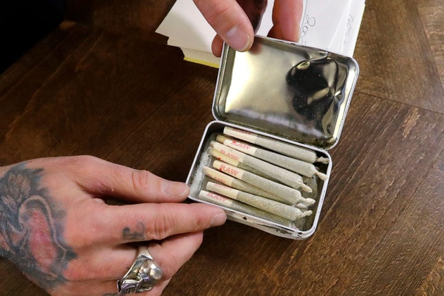 A clerk packs pre-rolled marijuana joints for a customer at the Medicinal Cannabis Dispensary, an unlicensed marijuana shop, in Vancouver, B.C. Around the province, authorities have visited 165 illegal dispensaries in the past year and warned them to get licensed or shut down. But despite a few raids, the government has been reluctant to close them all before more licensed shops open