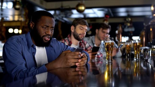 Sad multiethnic men surfing internet on phones in pub instead of communicating