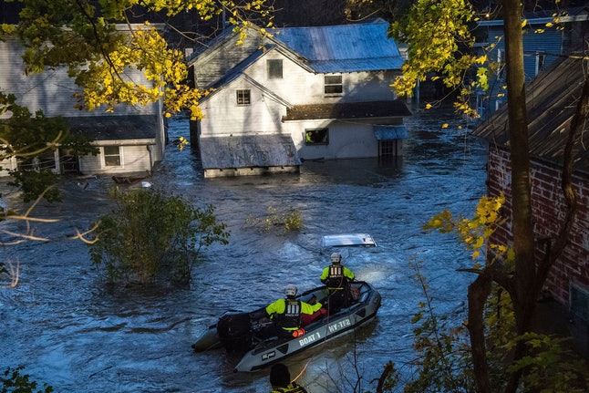 In this photo provided by the New York State Governor's Office, a man looks from a window of a house being flooded by rising waters of the East Canada Creek as police arrive in a rescue boat, in Dolgeville, N.Y. Several hundred people were being evacuated in scattered areas around the state because of high waters
