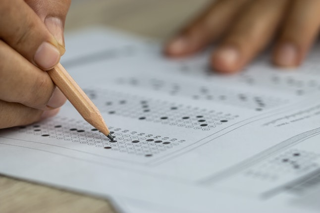 School Students hands taking exams, writing examination holding pencil on optical form of standardized test with answers sheet doing final exam in classroom. Education assessment Concept. Soft focus