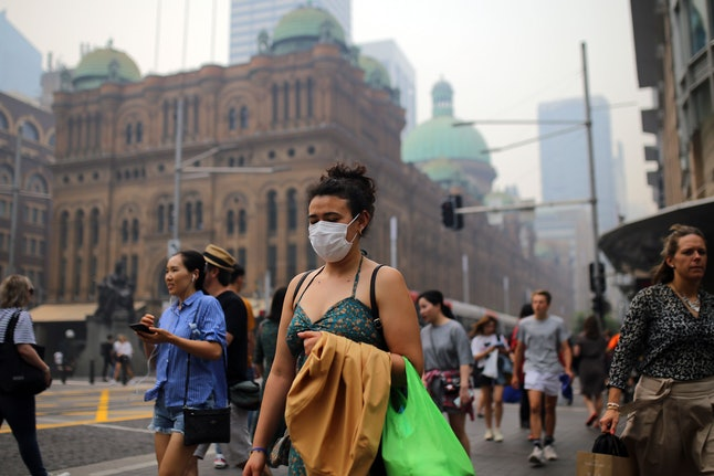 A pedestrian wears a mask as smoke and haze from bushfires in New South Wales blankets the CBD in Sydney, Australia, 10 December 2019. The New South Wales environment department says visibility across east and southwest Sydney was at a 'hazardous' level on Tuesday morning, while air quality was poor in southwest Sydney and hazardous in northwest Sydney.