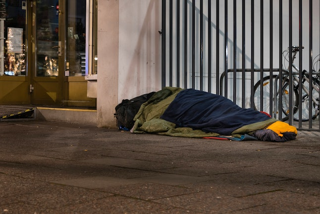 Sleeping Homeless Man, Homeless man in sleeping bag on sidewalk, homelessness in the city