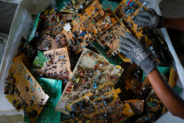 A worker picks up a motherboard seen in a basket before being shipped to Europe for safe processing at the recycling facility of the WEEE Center in Nairobi, Kenya, 03 December 2019 (issued 10 December 2019).