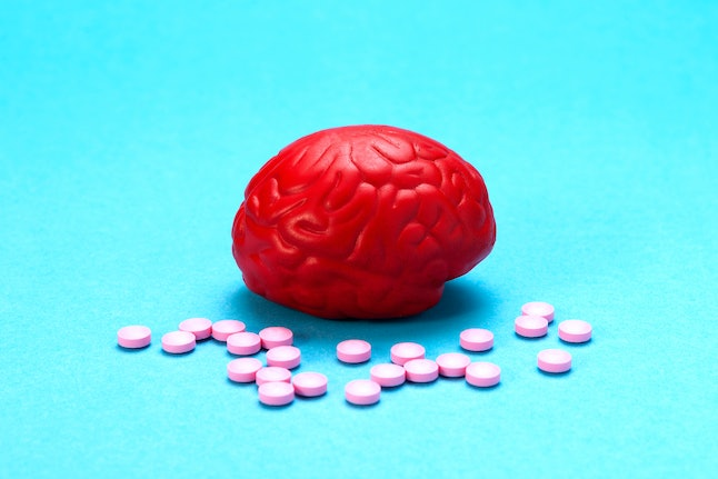 Red brain on a blue background with pink pills. Some pills for the brain. It is symbolic for drugs, psychopharmaceuticals, nootropics and other drugs. The medicine. Brain treatment