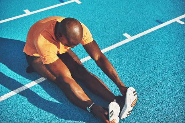 Focused young African male athlete in sportswear sitting alone on the lanes of a race track stretching his back before a run