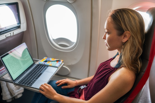 Young woman reading a book on laptop in plane
