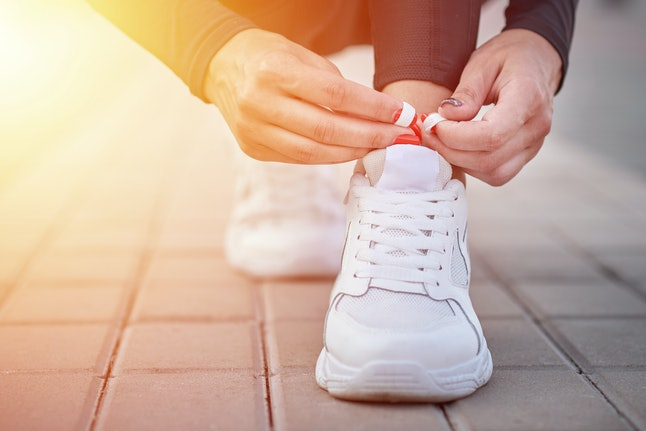 Woman get ready for run. Female hands tying shoelaces on sport sneakers