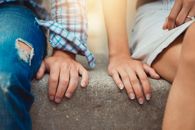 Hands of young couple in love close side by side on the first date. Loving couple has a happy relationships. First love concept.