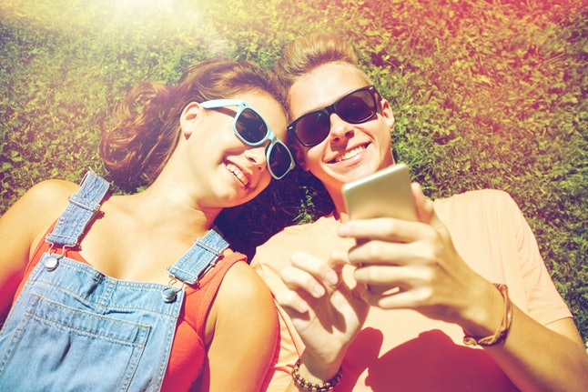 love and people concept - happy teenage couple in sunglasses with smartphone lying on grass at summer