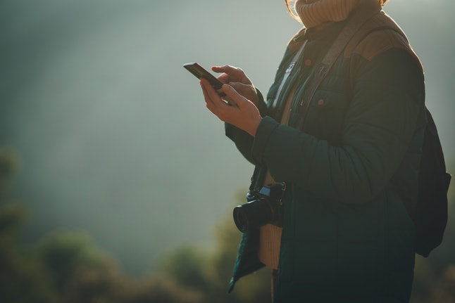 Crop picture of female traveller blogger with a camera holding modern mobile phone and posting photos from the forest trip above from the mountain, flare light and copy space for text or logo