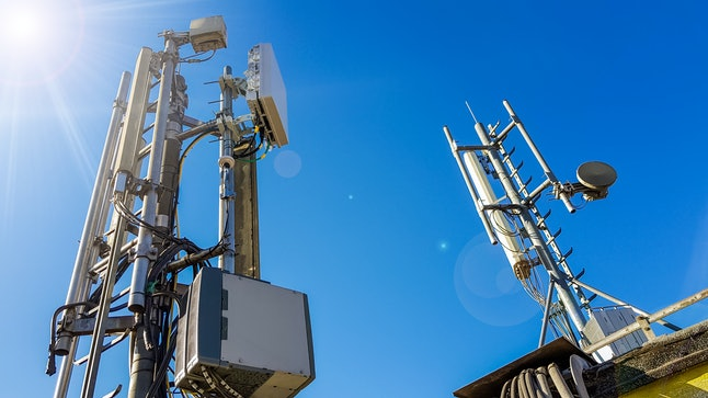 5G smart mobile telephone radio network antenna base station on the telecommunication mast radiating signal