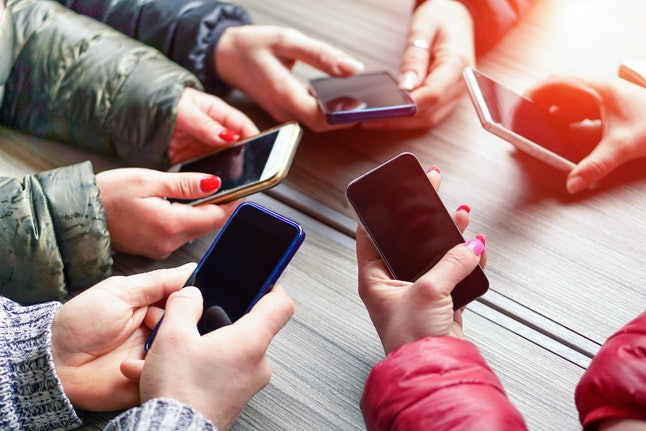Group of friends having fun together with smartphones - Closeup of hands social networking with mobile cellphones - Technology and phone addiction concept - Soft focus on the left bottom hand