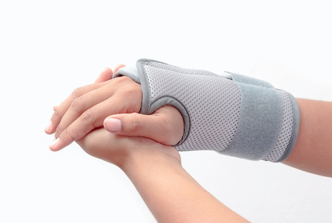 Woman's hand with wrist brace on white background
