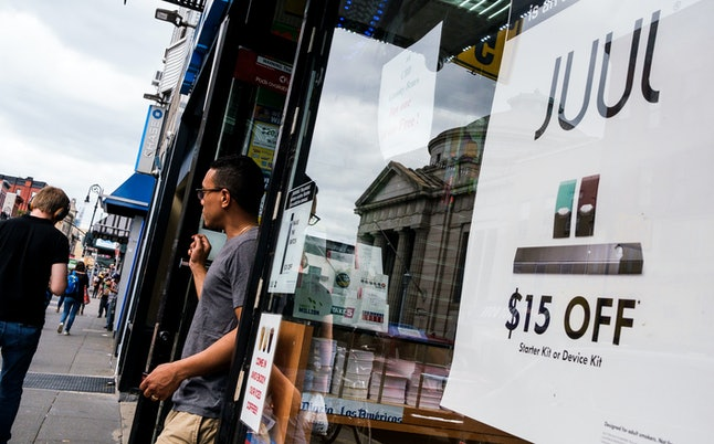 A sign advertises Juul pods, used for vaping in e-cigarettes, outside of a store in New York, New York, USA, 13 September 2019. The United States' Food and Drug Administration announced this week a developing plan that is expected to be introduced in the coming weeks that would ban the sale of flavored e-cigarettes and nicotine pods.