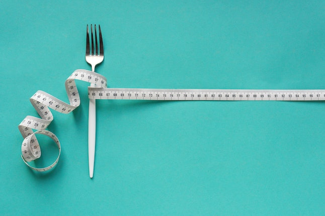 Fork and Measuring Tape on blue background, copy space. Diet, healthy lifestyle, weight loss concept with white fork and measuring tape.