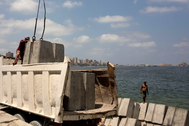 Workers prepare to place cement blocks to reinforce the sea wall against rising water levels on the corniche in Alexandria, Egypt. The Mediterranean city of Alexandria, which has survived invasions, fires and earthquakes since it was founded by Alexander the Great more than 2,000 years ago, now faces a new menace from climate change. Rising sea levels threaten to inundate poorer neighborhoods and archaeological sites, prompting authorities to erect concrete barriers out at sea to hold back the surging waves