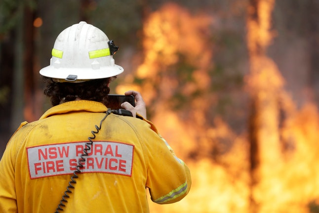 A firefighter uses his phone to record a controlled burn near Tomerong, Australia, in an effort to contain a larger fire nearby. Around 2,300 firefighters in New South Wales state were making the most of relatively benign conditions by frantically consolidating containment lines around more than 110 blazes and patrolling for lightning strikes, state Rural Fire Service Commissioner Shane Fitzsimmons said