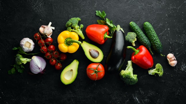 Ripe vegetables. Fresh vegetables on black stone background. Tropical fruits. Top view. Free space for your text.