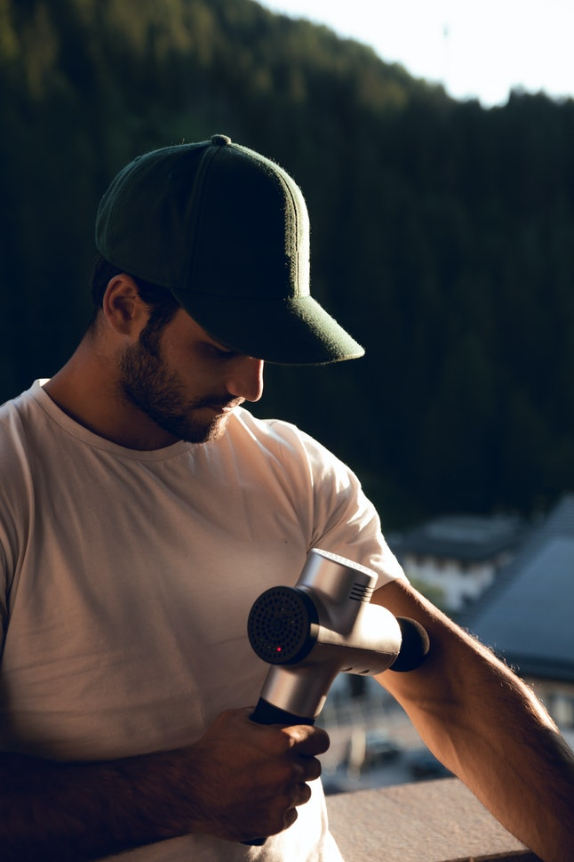Boy with cap and white shirt taking gray and black machine to massage his arm and body at sunset at home in Dolomites, Italy