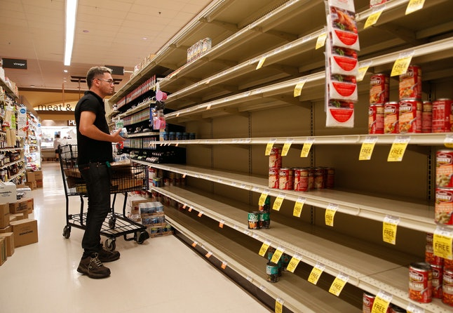 A worker looks at empty shelves for canned goods at a supermarket ahead of Hurricane Lane, in Honolulu