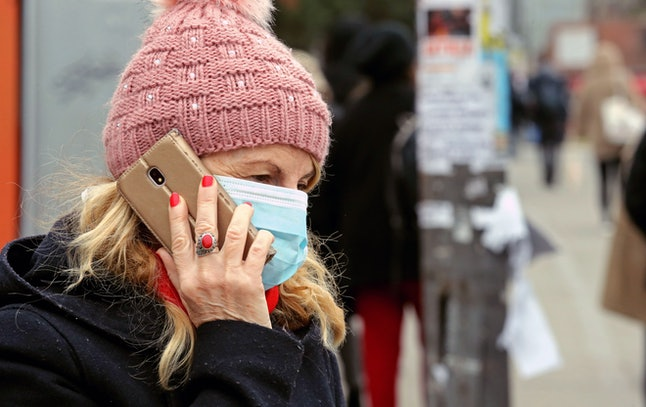 A woman wearing a surgical mask talks on the phone while waiting for a bus at a bus stop in Belgrade, Serbia, 14 March 2020. The first case of a Covid-19 Coronavirus in Serbia was recorded on March 6th, and acccording to the latest data from the Serbian Ministry of Health, positive cases reach 41, with no deaths or serious cases for now.