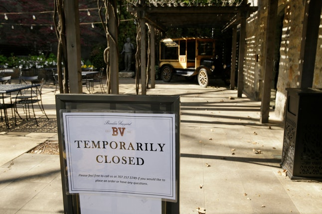 A temporarily closed sign is posted outside the entrance to the Georges De Latour Reserve Tasting Room at the Beaulieu Vineyard winery in Rutherfod, Calif. Wineries in the Napa Valley are closed due to coronavirus restrictions expect for production, but some allow customers to pick up shipments of wine and for direct purchases