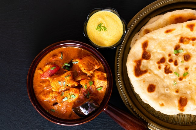 Food concept homemade Tandoori Chicken Masala curry with naan bread and yogurt dipping sauce with copy space