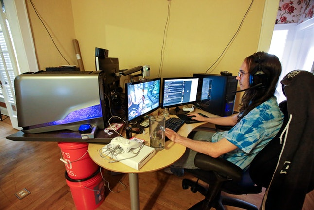 Brett Borden sits at a desk with multiple computers and video screens where he plays video games for a living, in Lakeland, Fla. Borden is one of three roommates that plays the games online to entertain others
