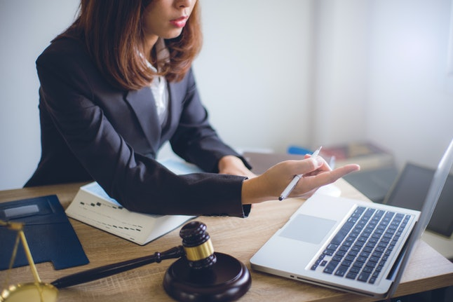 Lawyer sitting working with wooden gavel of judge and brass scale at the desk hand point working in laptop. lawyer and law ,judiciary and legislature courtroom legal concept.